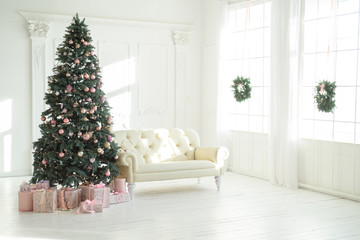 large white living room with a vintage sofa and a large Christmas tree with gifts and large panoramic windows