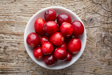 Bowl of cranberries on wooden table, from above