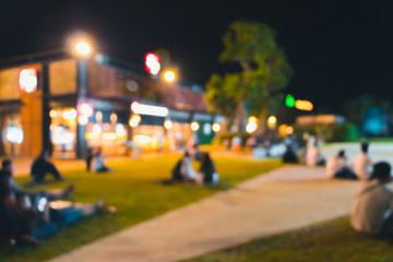blurred people dinner at park with festive lights for background