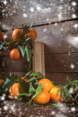 Tangerines with leaves on wooden box over old wooden table. Dark rustic style with falling snow and retro filter effect.