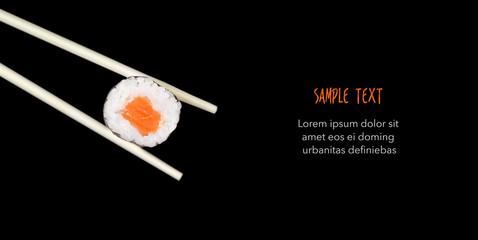 Chopsticks holding sushi isolated on black - Copyspace