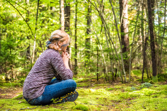 Young woman sitting on mossy ground in forest thinking