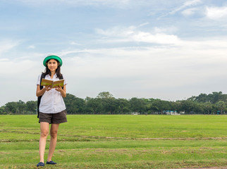 young woman carry backpack and reading book in green field, outd