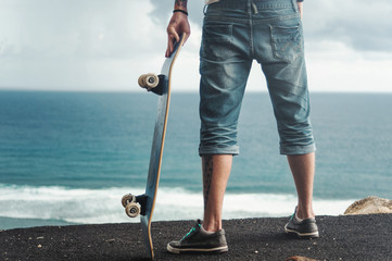 Back view of a skater standing on a high mountain in front of amazing ocean view
