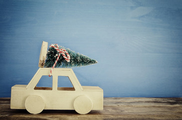 Wooden car carrying a christmas tree on the table