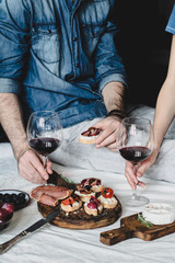 Couple having italian dinner with red wine and antipasto snacks set: bruschettas, crostini, prosciutto, camambert cheese, grapes and black olives. Selective focus, desaturated effect.