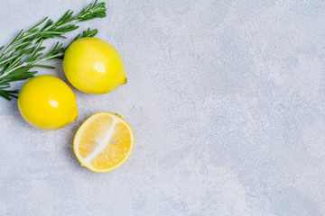 Fresh organic lemons and rosemary on bright blue stone background with copy space for text. Top view. Healthy ingredients for cooking