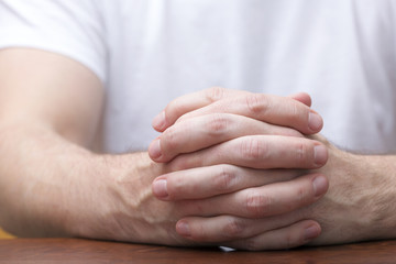 Man is sitting and holding his hands together on a wooden table. Like praying or in a meeting listening.