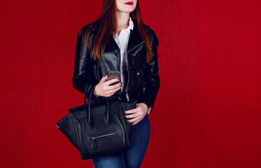 Wall Mural - fashion model posing in black leather jacket with bag