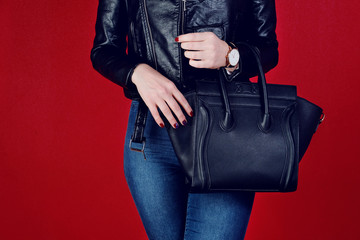 Wall Mural - Close up woman black leather big bag in hand.