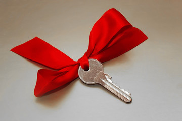 metal key with a red gift bow
