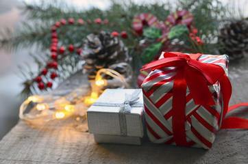 Christmas gift boxes.Christmas presents on old wooden table with blurred fir tree and garland in the background.Selective focus,copy space.Winter holidays,Merry Christmas or Happy New Year concept.