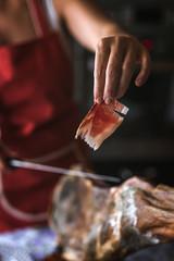 Unrecognizable woman slicing sliced ham