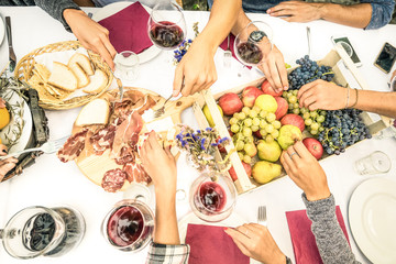 Top view of friend hands eating food and wine at barbecue garden party - People group enjoying fruit and sliced sausages at backyard meeting - Lunch and dinner concept outdoors - Bright vivid filter