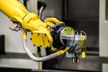 Industrial robot with CNC machine. Metal processing industry