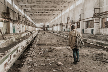 young boy stands in an abandoned building on repair of railway wagons. wandering boy. man in a protective cloak with a hood. Post apocalypse. traveling on foot in a post-apocalyptic world.