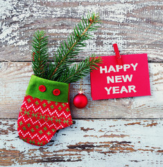 """Christmas decoration. Decorative red mitten, fir-tree branch with a ball and a red card with the inscription """"Happy New Year"""" on a rope against the background of the old removed board"""