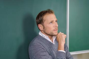 mann steht in der schule an der tafel und schaut nachdenklich nach oben