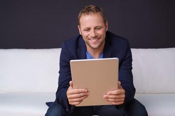 lächelnder mann liest auf seinem tablet