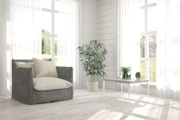 White room with armchair and green landscape in window. Scandinavian interior design