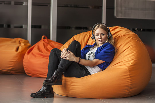 Armchair traditional bean bag for fun and relaxation  orange color. Young woman  with headphones while sitting on big cushioned frameless chair