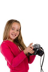 Young girl holding a vintage SLR camera laughing isolated on a white background