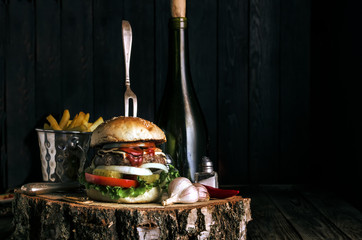 Delicious burger with fries and garlic on dark rustic background