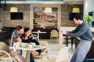 family, parenthood, technology, people concept - happy mother, father and little girl having dinner asked waiter to take picture by smartphone