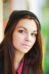 Portrait of long-haired, blue-eyed, dreamy young brunette woman in a cap posing on blurred background of the street, close up.