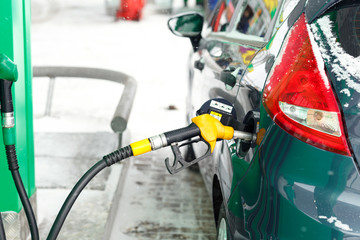 Car refueling on a petrol station in winter