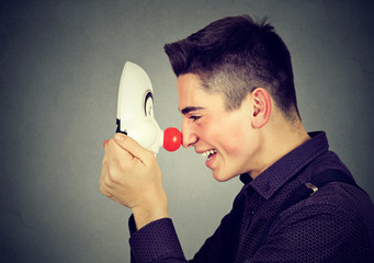 Laughing young man with clown mask