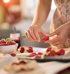 kitchen preparation: a woman makes tarts with strawberries