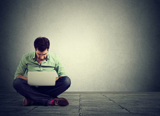 perfect technology. Man sitting on floor working on laptop computer