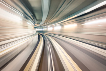 Subway underground tunnel with blurry rail tracks in metro gallery - Modern concept of public transport and connection - Radial zoomed speedness of railway space - Soft focus due to motion blur