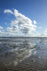 Maritime landscape with reflection of clouds in low tide water, Waddenzee, Friesland, The Netherlands