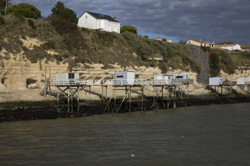 View from the Gironde estuary with the limestone cliff of the village of Meschers sur Gironde and its troglodytic houses and traditionnal typical wooden fisherman cabin, Charente maritime, France