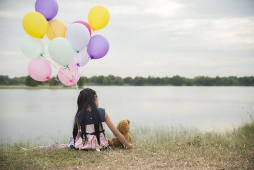 A little girl holding balloons of many colors ,hug teddy bear on grass.The front is reservoir.