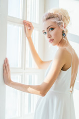 young beautiful blonde woman posing in white Studio. Portrait wi