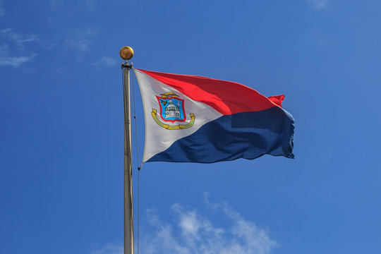 St. Maarten flag in blue sky.