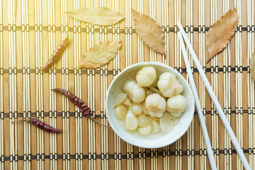 pickled garlic , decorated picture with bay leaves and dry chilies on a bamboo tray, Asian food popular eat with rice soup
