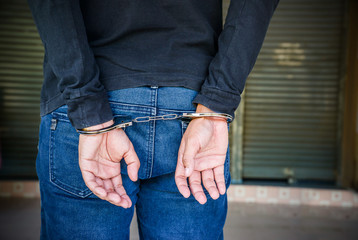 Male hands locked in handcuffs, Outlaw's hands in handcuffs.