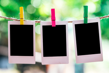 3 Blank instant photo and clippaper hanging on the clothesline with bokeh nature background.Designer concept.
