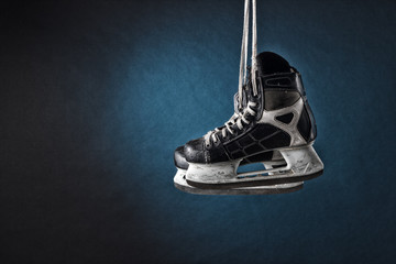 Men's hockey skates hanging on a dark background.