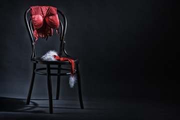 Women's underwear and hat of Santa Claus hanging on a retro chair. Erotic Christmas motif.