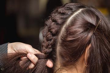 Hairdresser making a braid on long brunette hair in barber salon