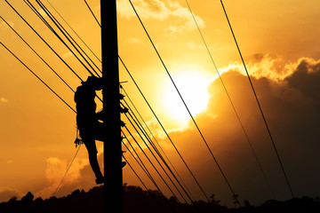 silhouette of electrician working on electric power pole
