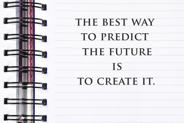 Inspirational motivating quote on spring white note book. The best way to predict the future is to create it..