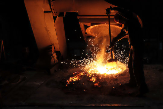 Foundry worker melting metal for casting spare parts.