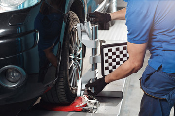 Grid sensor sets mechanic on auto. Car stand with sensors wheels for alignment camber check in workshop of Service station.