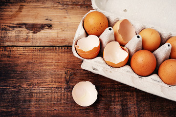 Chicken eggs and shells of broken eggs in a cardboard tray on a wooden table surface. Eggs